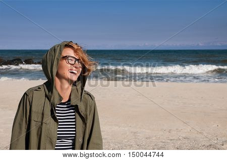 Happy woman in warm clothes jacket on the beach against the ocean in the cold season enjoying a walking by the beach sea in autumn