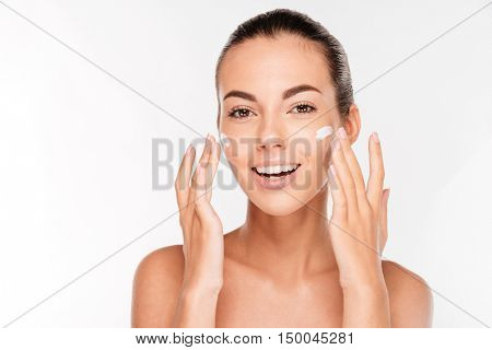 Beautiful young woman applying cosmetic cream treatment on her face isolated on white background