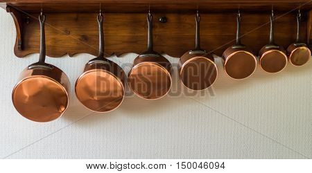 set of saucepans hanging from a rack in the kitchen
