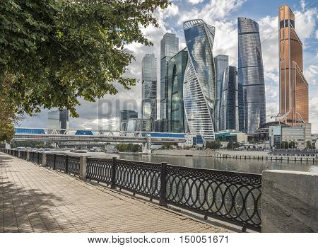 Green trees along the pedestrian sidewalk on the Waterfront of Taras Shevchenko on the background of Moscow city. poster
