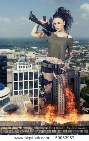 Beautiful young tattooed woman holding an automatic assault rifle