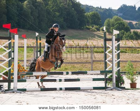 Portrait of girl riding pony on showjumping competition