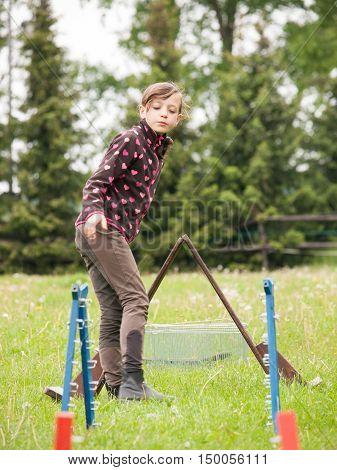 Young girl preparing hurdles for rabbit jumping