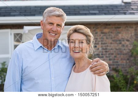Portrait of a happy senior couple smiling in front of their house. Older couple embracing and looking at camera. Happy old retired couple hugging. poster