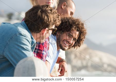 Close up of a young multi ethnic guy having fun with friends near beach. Group of happy young man and woman standing facing sea while leaning over fence. Happy african man looking at camera outdoor.
