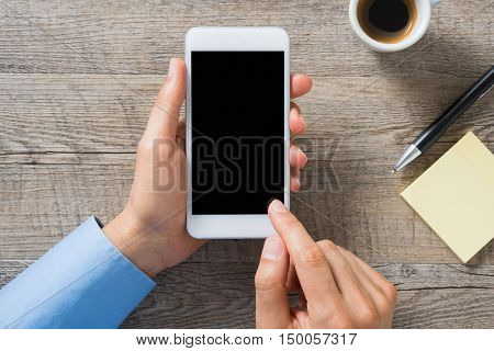 Closeup of man using smartphone on desk. Top view of businessman using smart phone with coffee cup and sticky notes on wooden table. High angle view of man typing on cellphone, empty blank screen.