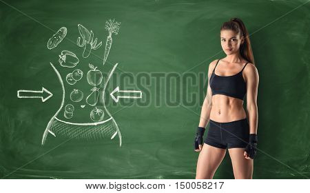 Fitness girl on background of blackboard with healthy food sketches. Reduction of waist. Slim and healthy body. Healthy lifestyle concept.