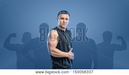 Young fitness man standing sideways and showing thumb up. Inwardness. Self-perfection. Self improvement. Fitness and sport.