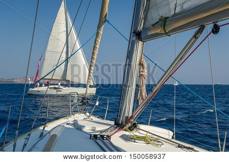 View from one sailing yacht deck to another. Cruising boats at Mediterranean sea waters.