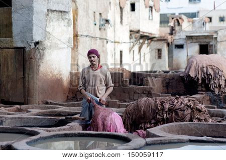 FEZ, MOROCCO - JANUARY 4, 2014: Man working hard in the tannery souk in Fez, Morocco