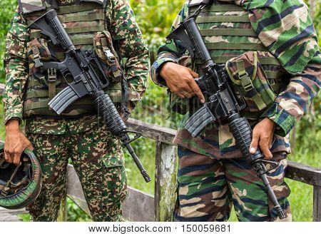 Kota Kinabalu, Malaysia - June 21, 2016: Assault rifles in the hands of two unrecognised soldiers