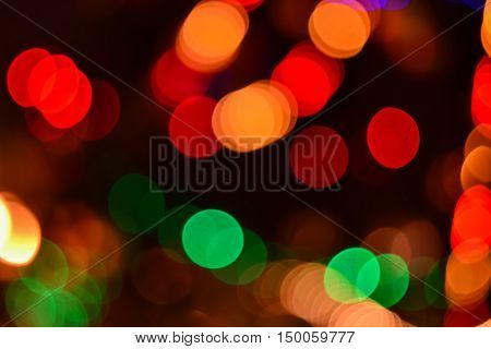 Christmas multicolored glittering spots background in dark