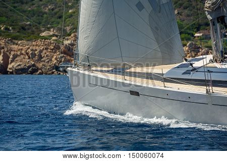 Luxury new cruising sailboat bow with teak deck under hoisted sails and some heeling, bow view from port side. Sardinia, Italy.