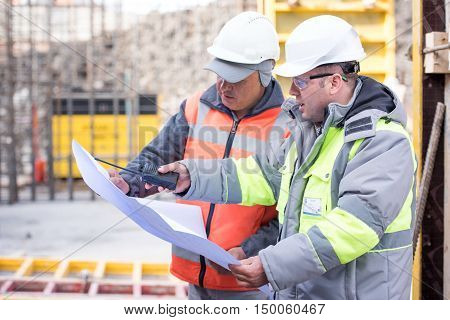 Civil engineer And Foreman at construction site are inspecting ongoing works according to design drawings.
