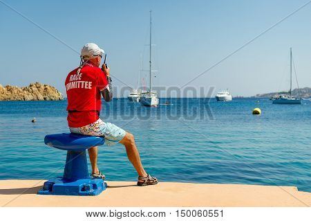 Sailing race referee watching at the yachts at anchorage in beautiful Sardinian bay. Italy.