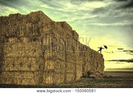 Person balancing on straw bales with an umbrella.