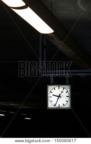 Contrast Diagonal Flourescent Lights Leading to Square Geometric Clock Time Architecture