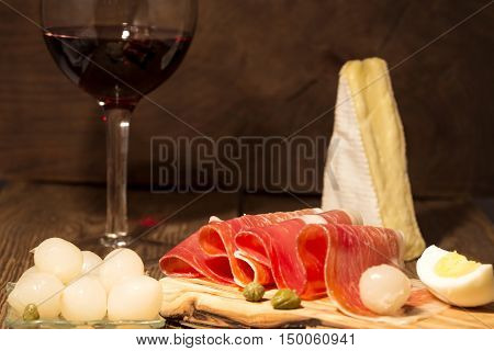 Prosciutto appetizer with a glass of red wine