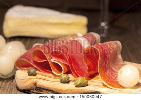 Prosciutto appetizer with camembert and the pickled baby onions