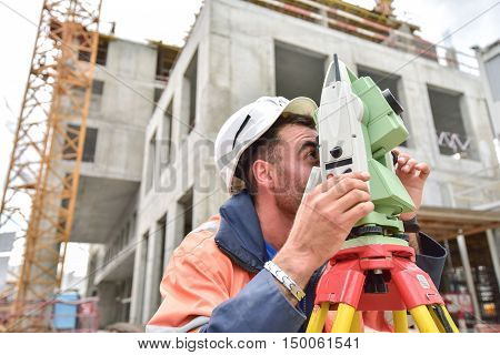 Surveyor at at construction site is inspecting ongoing production