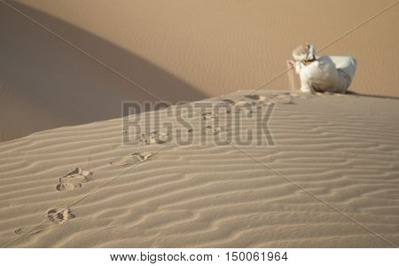 Man in traditional outfit in a desert at sunrise playing with sand