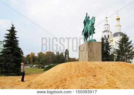 Orel Russia - October 01 2016: Man watching Ivan the Terrible monument installed on heap of sand near Orthodox church horizontal