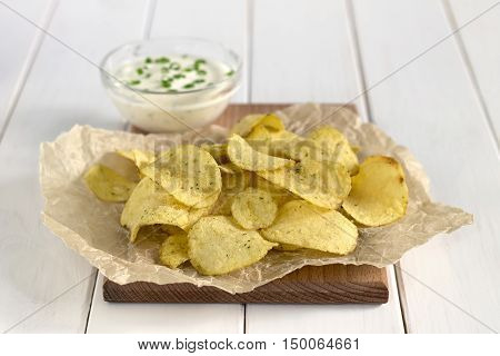 Potato Chips With Dipping Sauce On A White Table.