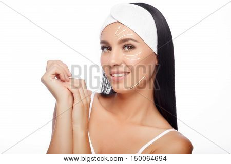 Young Woman in Hairband Touching her Face with a Perfectly Clean Skin. Beautiful Woman Cares for the Skin Face. Skin Care, Cosmetics and Makeup Concept.