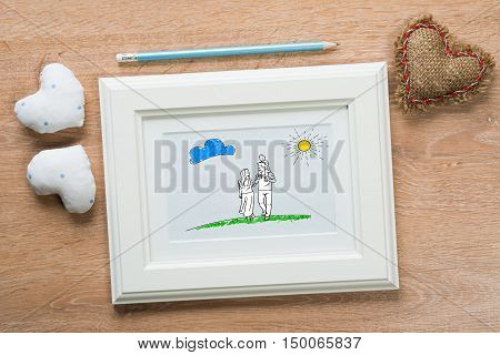 Photo frame with happy couple drawing on wooden table