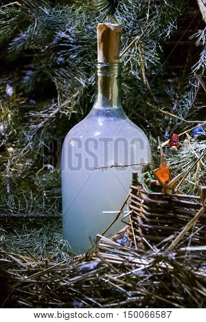 Holiday bottle of homemade strong drink vodka moonshine hooch near Christmas tree. Still life