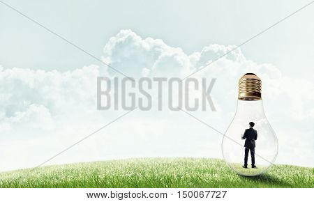 Businessman inside glass light bulb outdoors looking away