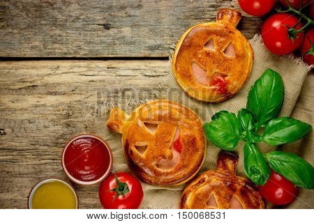 Jack-o'-Lantern vegetables ham mini pizza for Halloween party on old wooden table top view blank space for text