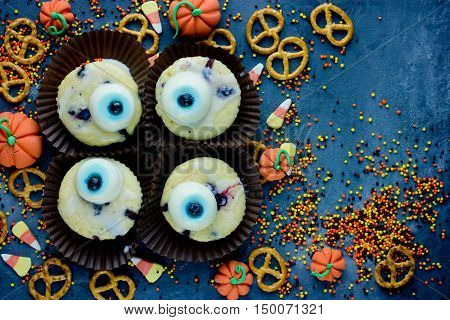 Halloween background healthy sweets and treats for kids funny one eye cupcakes creative food idea top view blank space for text
