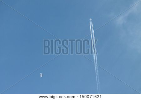 a jet flying in front of the moon with a few clouds over a blue sky