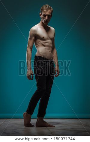Model Tests. Handsome Man In Black Jeans With Perfect Body Posing On Blue Background
