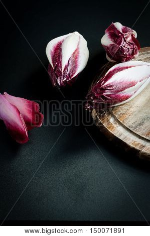 Three radicchio heads and wooden cutting board on black background