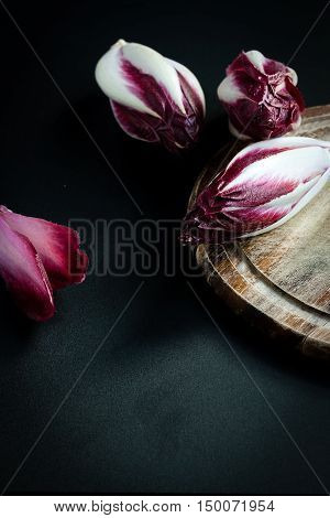 Radicchio salad and wooden cutting board on the black background