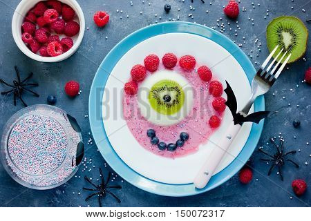 Halloween funny dessert recipe -scary eye semisphere jelly with kiwi and raspberry sauce creative idea for kids party top view