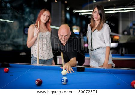 Man with two beautiful girl in a billiard hall playing snooker
