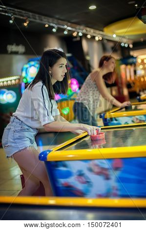 Young woman playing a game of air hockey in the game room
