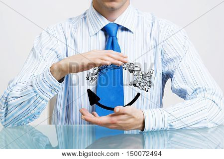 Businessman in suit sitting at desk making protective gesture with palms