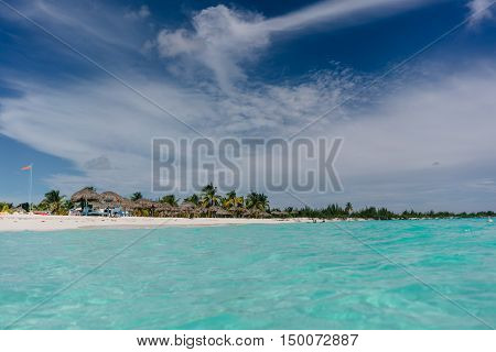 The boat in the waters of the Caribbean Sea and the view of the beach of Cayo Largo, Cuba out of the water
