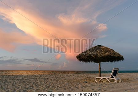 Umbrella on the beach in the sunset hours, Cuba