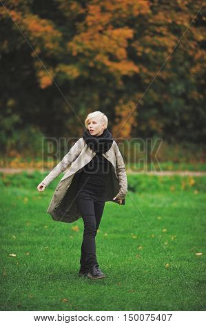 Young attractive blonde girl enjoys spending time in autumn Park.