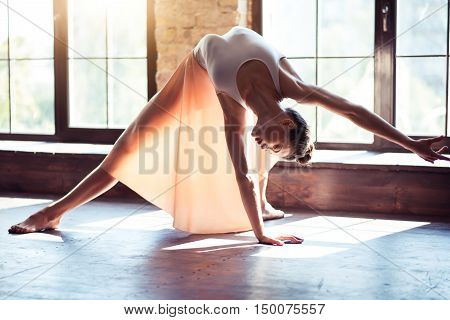 Keeping balance. Beautiful slender female dancer standing near the window and bending backwards while dancing