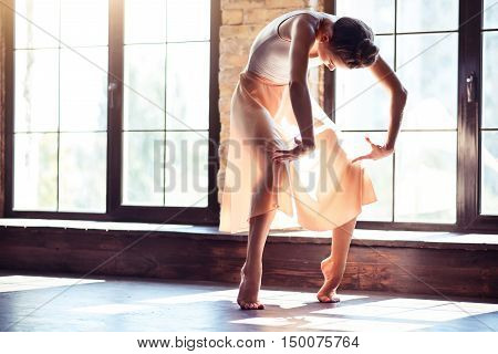 Beautiful movements. Skillful nice attractive woman standing on tiptoes and bending forward while dancing