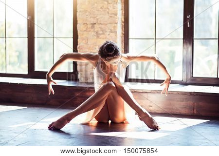 Beauty in plasticity. Professional attractive brunette dancer crossing her legs and moving her arms while sitting on the floor