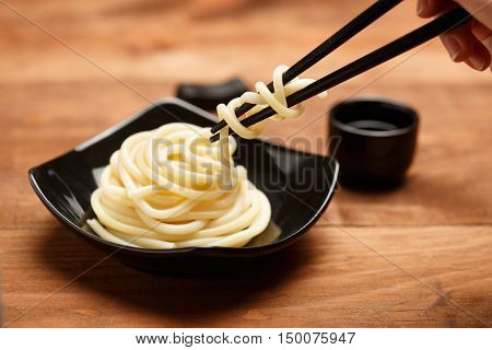 Spaghetti macaroni taking from black ceramic dish by chopsticks at wooden table background with sake cup. Shallow dof. Focus on chopsticks.