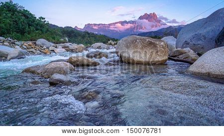 Landscape of Melangkap river with transparent water,rocky bottom and with Mount Kinabalu at the background in Kota Belud Sabah Malaysian Borneo.