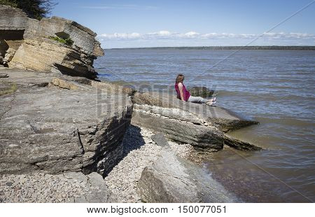 horizontal image of a woman sitting on large boulder next to a lake just enjoying the peace and quiet on a summer afternoon.